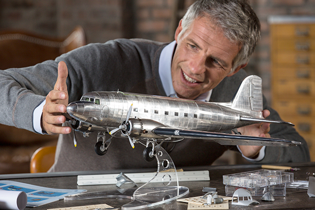 Man admiring a 1:32 Douglas DC3 scale model plane, as part of a blog about choosing your first scale model.