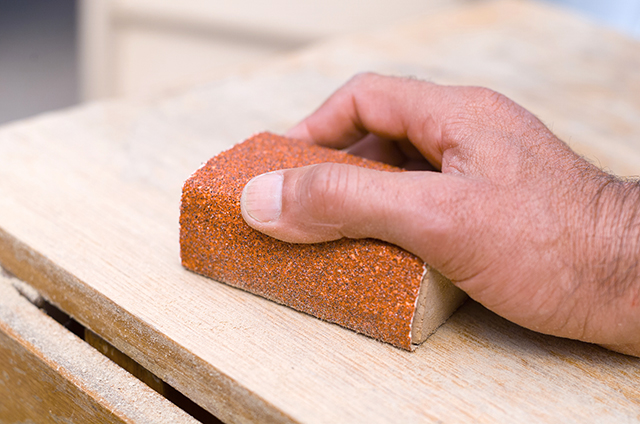 Image of man using a sandblock to sand wood, as part of a blog about abrasives and how to sand scale models.