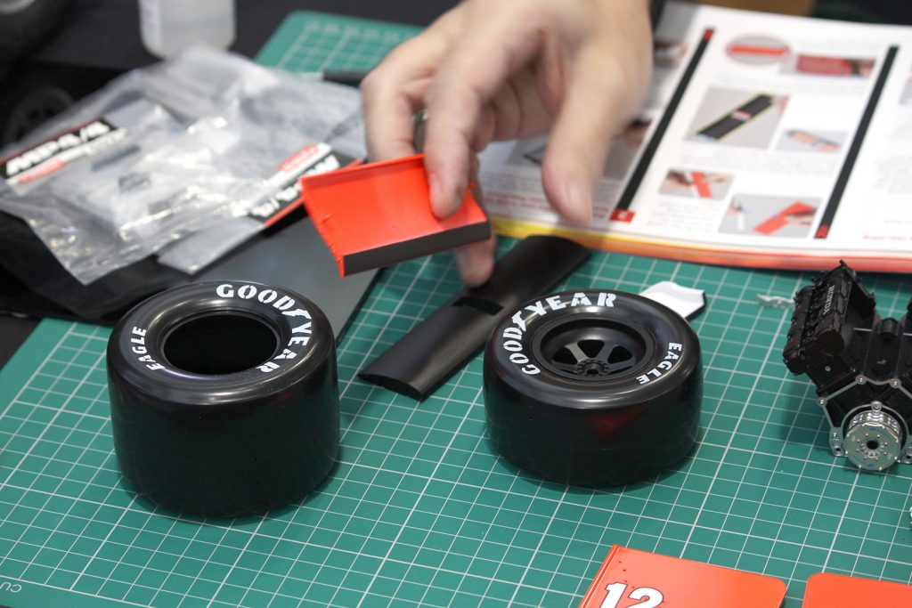 Image of man's hand building the ModelSpace Senna McLaren MP4/4 scale model, as part of a blog about activities to do at home.