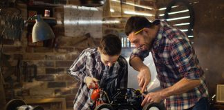 Image of a father and son work on a remote controlled scale model car in a workshop, as part of a blog about creating a scale modelling workspace.