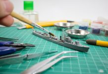 Image of person painting scale model ship, as part of a blog about how to paint model kits.
